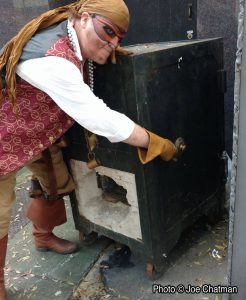 Captain Drew wrestles with a giant old-fashioned safe on the sidewalk. The side of the safe appears to have been blown open.